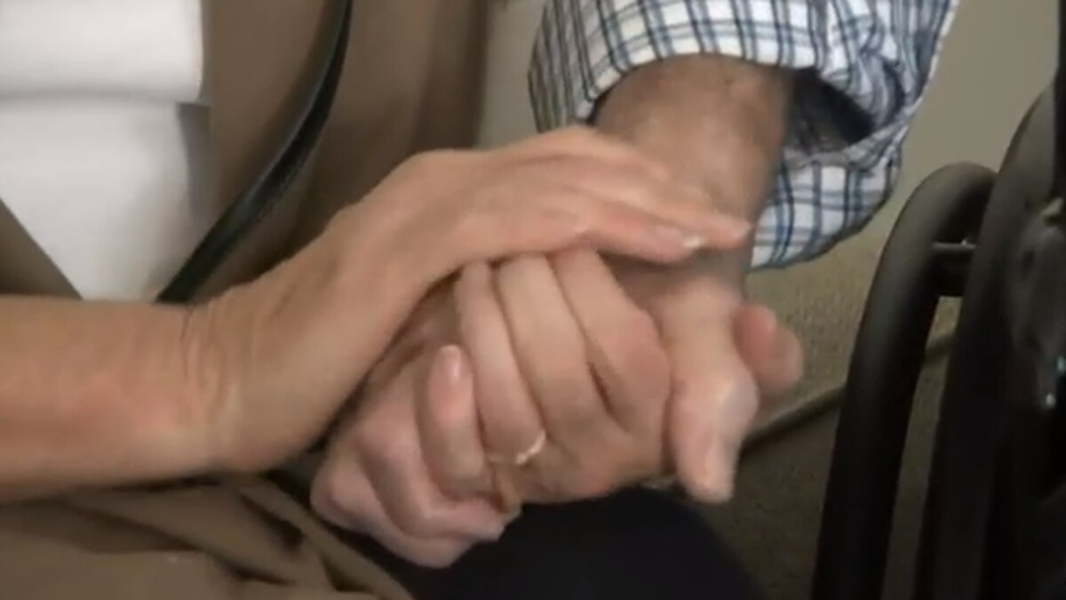 Husband and wife hold hands