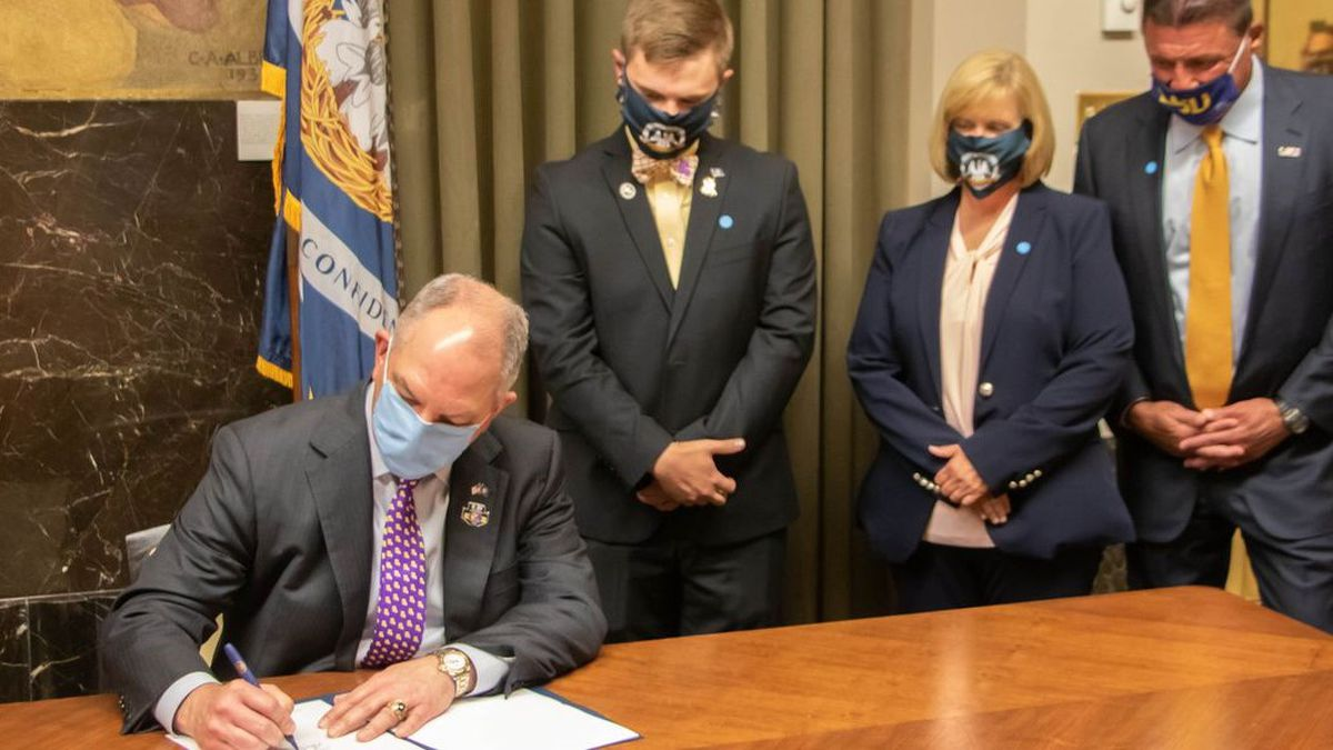 Gov. Edwards signs late Rep. Reggie Bagala LSU license bill into law during a private ceremony with Bagala's wife and son, LSU head football coach Ed Orgeron, and Athletic Director Scott Woodard Wednesday, June 10, 2020.
