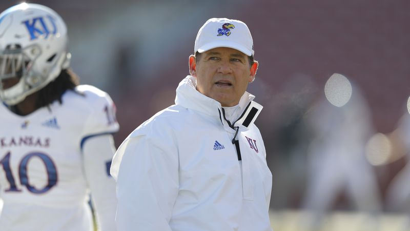 Kansas head coach Les Miles watches warm ups before an NCAA college football game against Iowa...