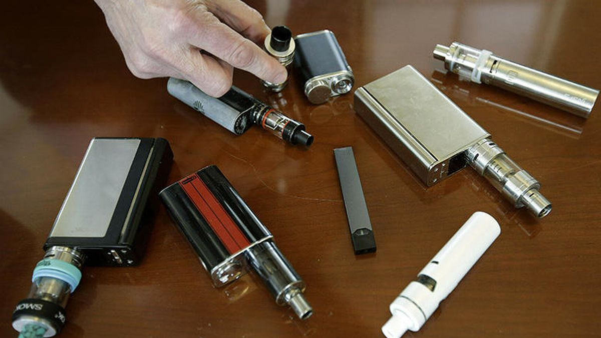 In this April 10, 2018, file photo, a high school principal displays vaping devices that were confiscated from students in such places as restrooms or hallways at the school in Massachusetts. (Source: AP Photo/Steven Senne, File)