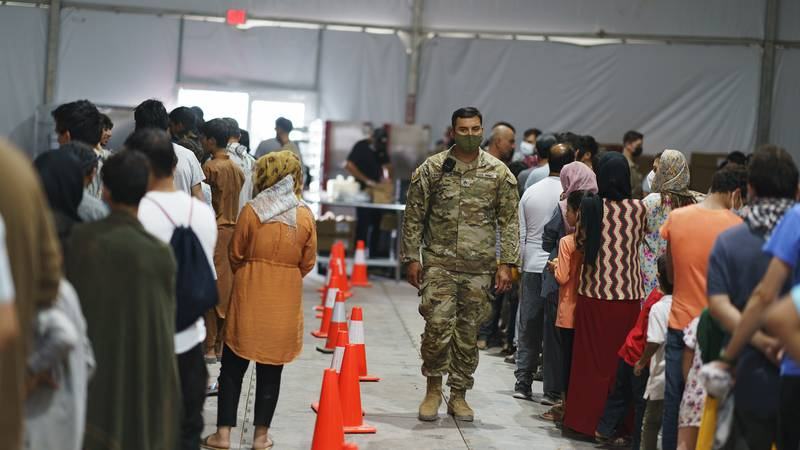 Afghan refugees line up for food in a dining hall at Fort Bliss' Doña Ana Village where they...
