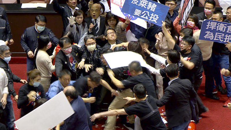 In this image made from video, lawmakers fight during a parliament session in Taipei, Taiwan,...