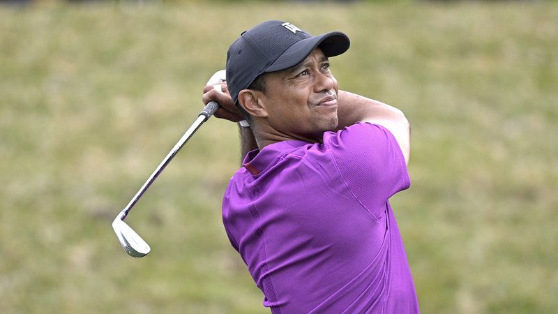 Tiger Woods watches his tee shot on the 17th hole during the first round of the PNC...