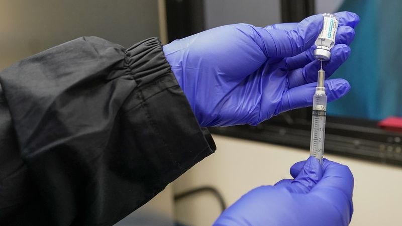 FILE - In this March 31, 2021 file photo, a nurse fills a syringe with a dose of Johnson &...