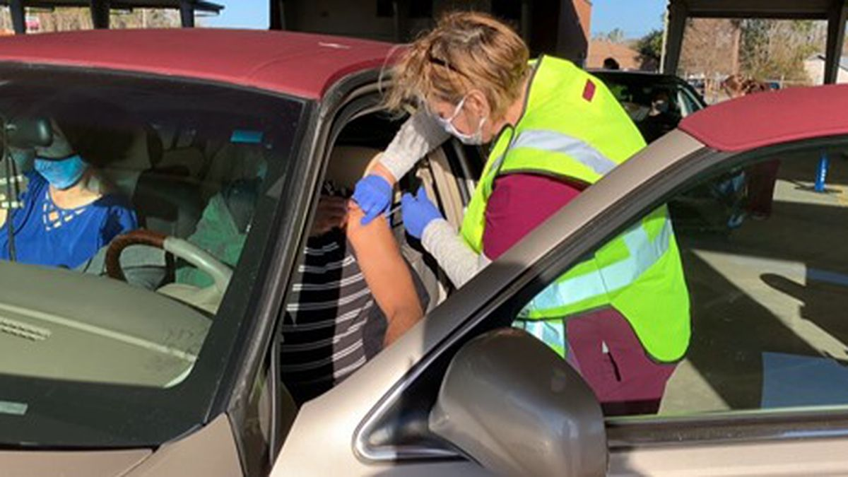 Photo: A vaccine being administered to someone sitting in a car.