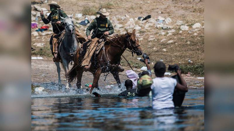 U.S. Customs and Border Protection mounted officers attempt to contain migrants as they cross...