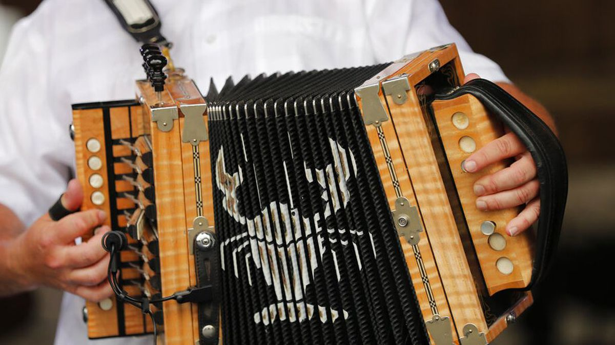 Jimmy Breaux plays an accordion with a depiction of a crawfish as he plays with Johnny Sonnier...