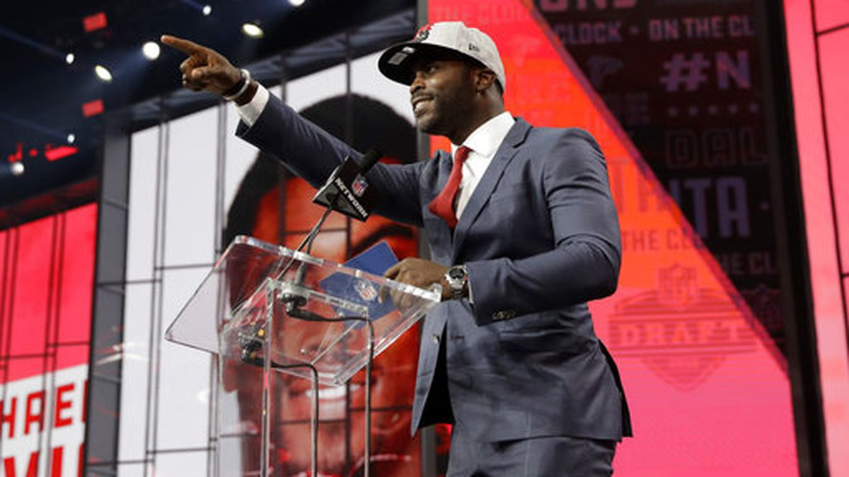 Former Atlanta Falcons player Michael Vick gestures to Falcons fans as he announces Colorado's Isaiah Oliver as the team's pick during the second round of the NFL football draft Friday, April 27, 2018, in Arlington, Texas. (AP Photo/Eric Gay)